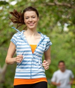 Athletic woman running at the park smiling